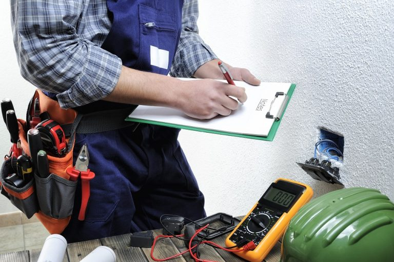 Young electrician takes notes while working in a residential electrical installation